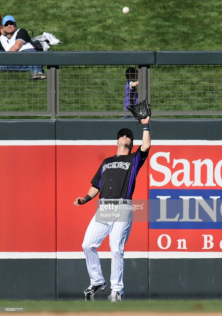 Corey Dickerson #77 of the Colorado Rockies catches a fly ball against the Texas Rangers at Salt River Field on February 25, 2013 in Scottsdale, Arizona.