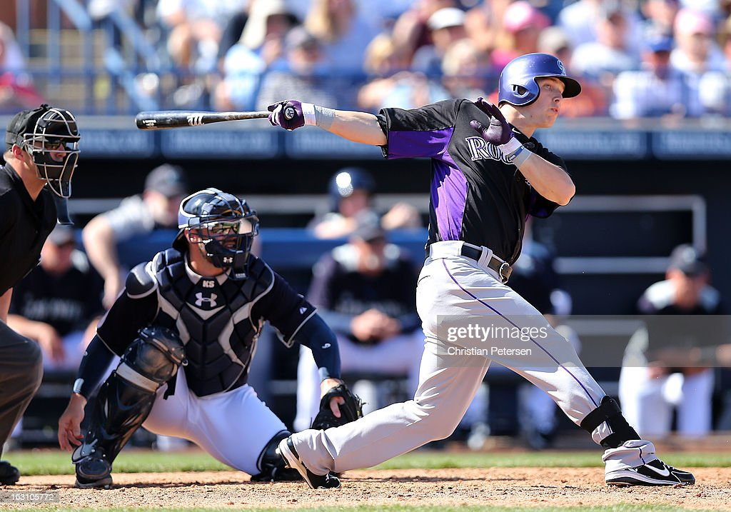 Corey Dickerson #77 of the Colorado Rockies hits a RBI single against the Seattle Mariners during the fourth inning of the spring training game at Peoria Stadium on March 4, 2013 in Peoria, Arizona.