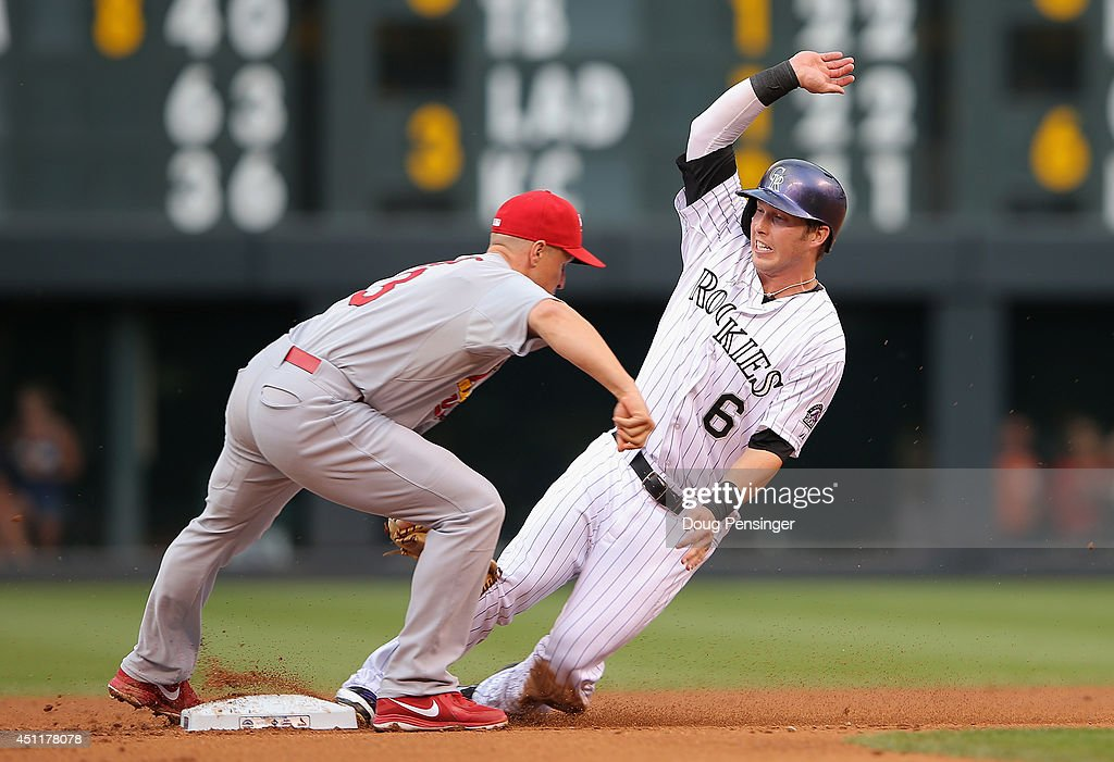 Corey Dickerson #6 of the Colorado Rockies is tagged out by second baseman Mark Ellis #3 of the St. Louis Cardinals while attempting to steal second base in the first inning at Coors Field on June 24, 2014 in Denver, Colorado.