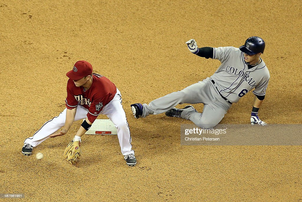 Corey Dickerson #6 of the Colorado Rockies safely slides into second base after hitting a double ahead of Aaron Hill #2 of the Arizona Diamondbacks during the 10th inning of the MLB game at Chase Field on April 30, 2014 in Phoenix, Arizona. The Diamodbacks defeated the Rockies 5-4 in 10 innings.