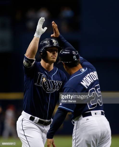 Corey Dickerson of the Tampa Bay Rays celebrates his home run off of pitcher JC Ramirez of the Los Angeles Angels with third base coach Charlie...