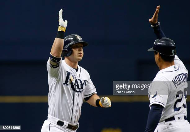 Corey Dickerson of the Tampa Bay Rays celebrates his tworun home run with third base coach Charlie Montoyo during the third inning of a game against...