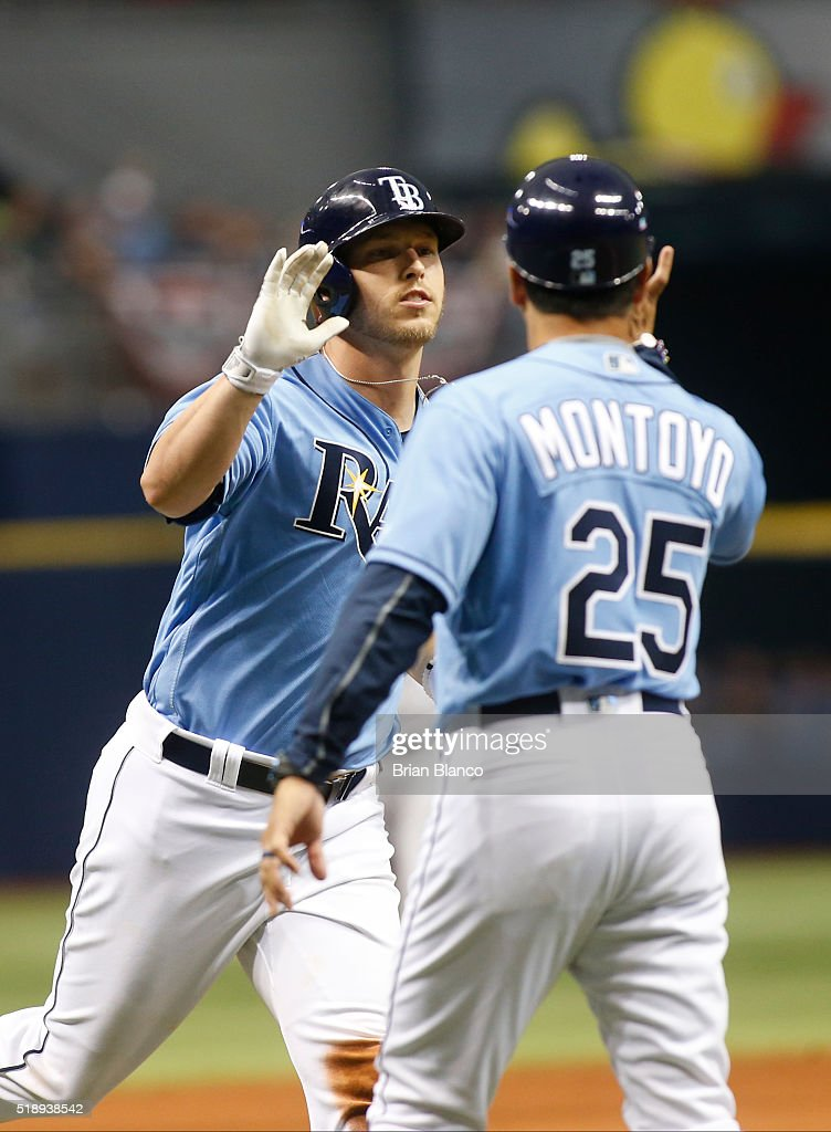 Corey Dickerson #10 of the Tampa Bay Rays celebrates with third base coach Charlie Montoyo #25 after hitting a home run during the ninth inning of a game against the Toronto Blue Jays on April 3, 2016 at Tropicana Field in St. Petersburg, Florida.