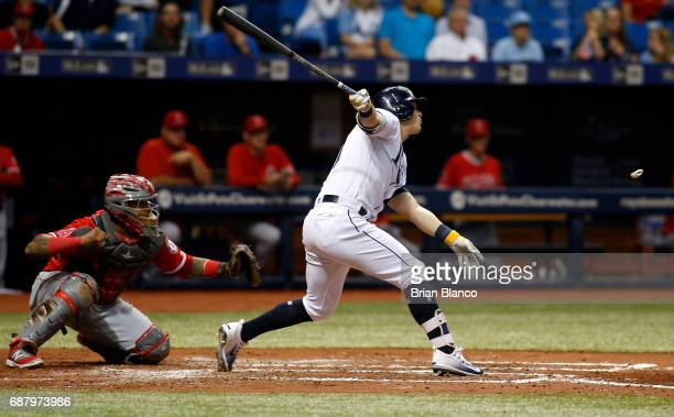 Corey Dickerson of the Tampa Bay Rays hits a double in front of catcher Martin Maldonado of the Los Angeles Angels of Anaheim during the third inning...