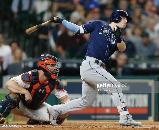 Corey Dickerson of the Tampa Bay Rays singles in a run in the second inning as Evan Gattis of the Houston Astros watches at Minute Maid Park on...