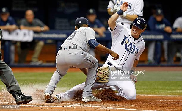 Corey Dickerson of the Tampa Bay Rays slides in safely on a passed ball ahead of an attempted tag by Edwin Diaz of the Seattle Mariners during the...