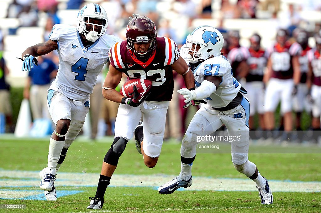 <a gi-track='captionPersonalityLinkClicked' href=/galleries/search?phrase=Corey+Fuller&family=editorial&specificpeople=2599798 ng-click='$event.stopPropagation()'>Corey Fuller</a> #83 of the Virginia Tech Hokies avoids a tackle by Jabari Price #4 and Darien Rankin #27 of the North Carolina Tar Heels on October 6, 2012 at Kenan Stadium in Chapel Hill, North Carolina.