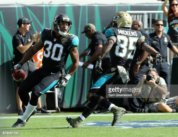 Corey Grant and Jaydon Mickens of the Jacksonville Jaguars celebrate after Grant had a 56yard touchdown run during the first half of their game...