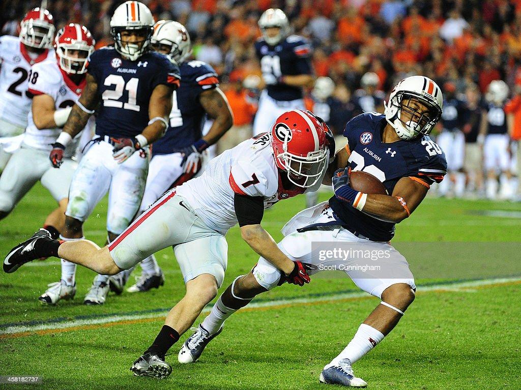 Corey Grant #20 of the Auburn Tigers is tackled by Blake Sailors #7 of the Georgia Bulldogs at Jordan-Hare Stadium on November 16, 2013 in Auburn, Alabama.