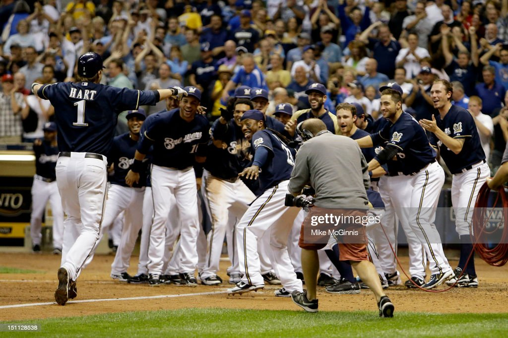 Corey Hart #1 of the Milwaukee Brewers is awaited by the team at home plate after hitting a walk off home run in the bottom of the 9th inning putting the Brewers up 3-2 over the Pittsburgh Pirates during the game at Miller Park on September 01, 2012 in Milwaukee, Wisconsin.