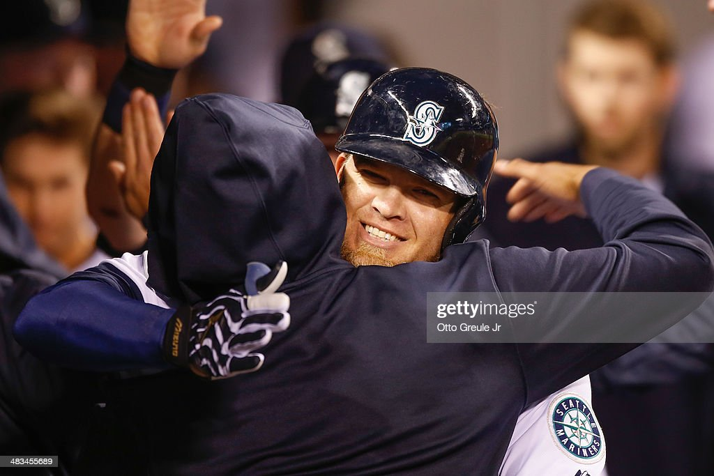 Corey Hart #27 of the Seattle Mariners is congratulated by teammates after hitting a three-run homer in the third inning against the Los Angeles Angels of Anaheim on Opening Day at Safeco Field on April 8, 2014 in Seattle, Washington.