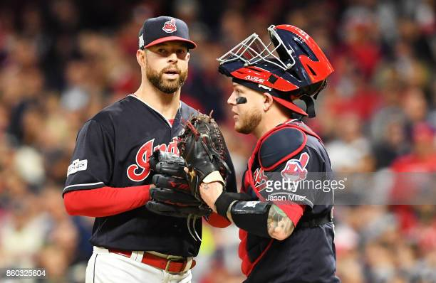 Corey Kluber talks to Roberto Perez of the Cleveland Indians on the mound in game five of the American League Divisional Series against the New York...