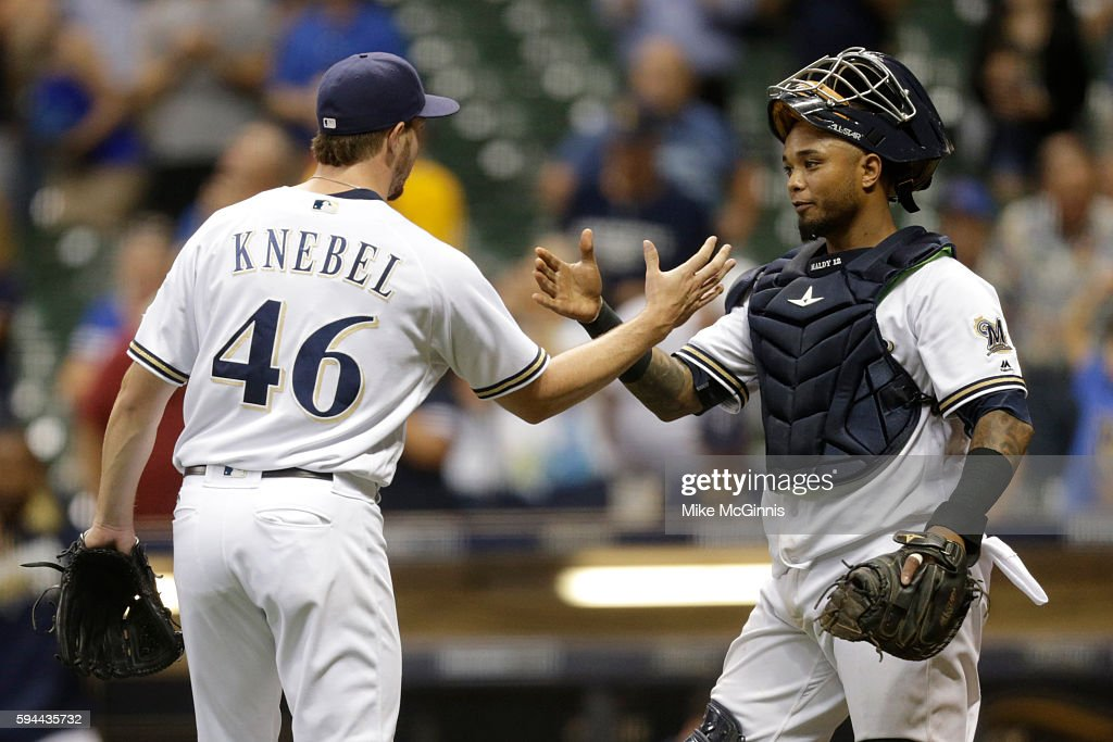 Corey Knebel of the Milwaukee Brewers celebrates with Martin Maldonado after the 64 win over the Colorado Rockies at Miller Park on August 23 2016 in...