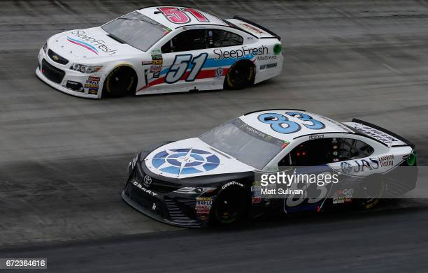 Corey LaJoie driver of the JAS Expedited Trucking Toyota races Timmy Hill driver of the SleepFresh Mattress Chevrolet during the Monster Energy...
