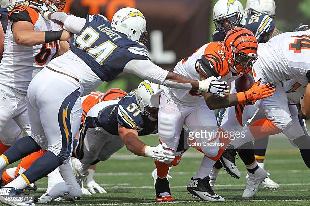 Corey Liuget of the San Diego Chargers and Kyle Emanuel of the San Diego Chargers combine to tackle Jeremy Hill of the Cincinnati Bengals during the...