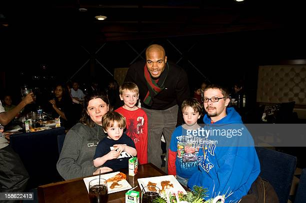 Corey Maggette of the Detroit Pistons visits with a familiy during the Detroit Pistons Toys for Tots Holiday event for metro Detroit families at the...