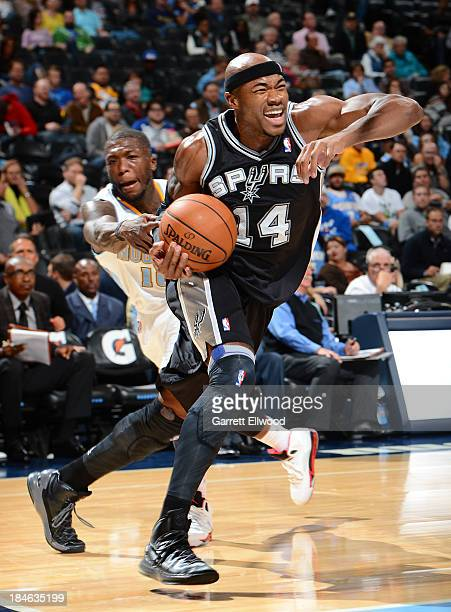Corey Maggette of the San Antonio Spurs drives to the basket against Nate Robinson of the Denver Nuggets on October 14 2013 at the Pepsi Center in...