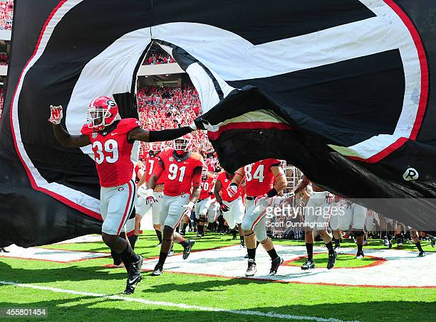 Corey Moore of the Georgia Bulldogs leads his team on to the field to play the Troy Trojans at Sanford Stadium on September 20 2014 in Athens Georgia