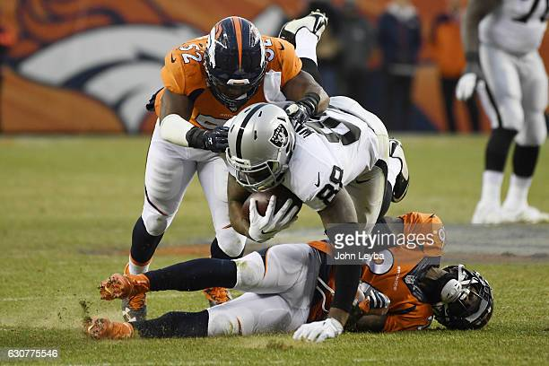 Corey Nelson of the Denver Broncos and Darian Stewart tackle Clive Walford of the Oakland Raiders during the third quarter on Sunday January 1 2017...