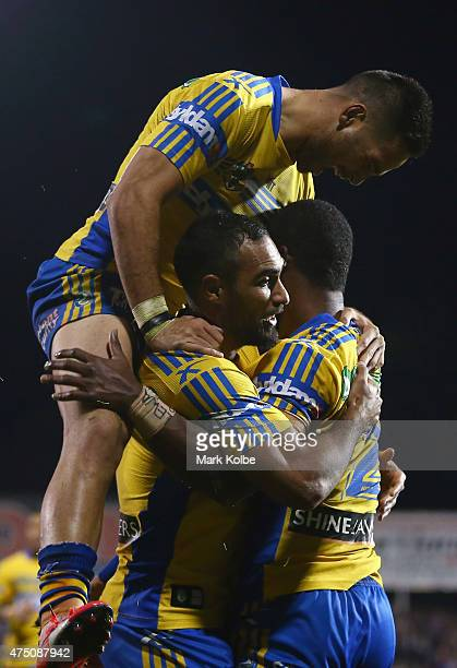 Corey Norman and Reece Robinson of the Eels congratulate Semi Radradra of the Eels as he celebrates with his team mates after scoring a try during...