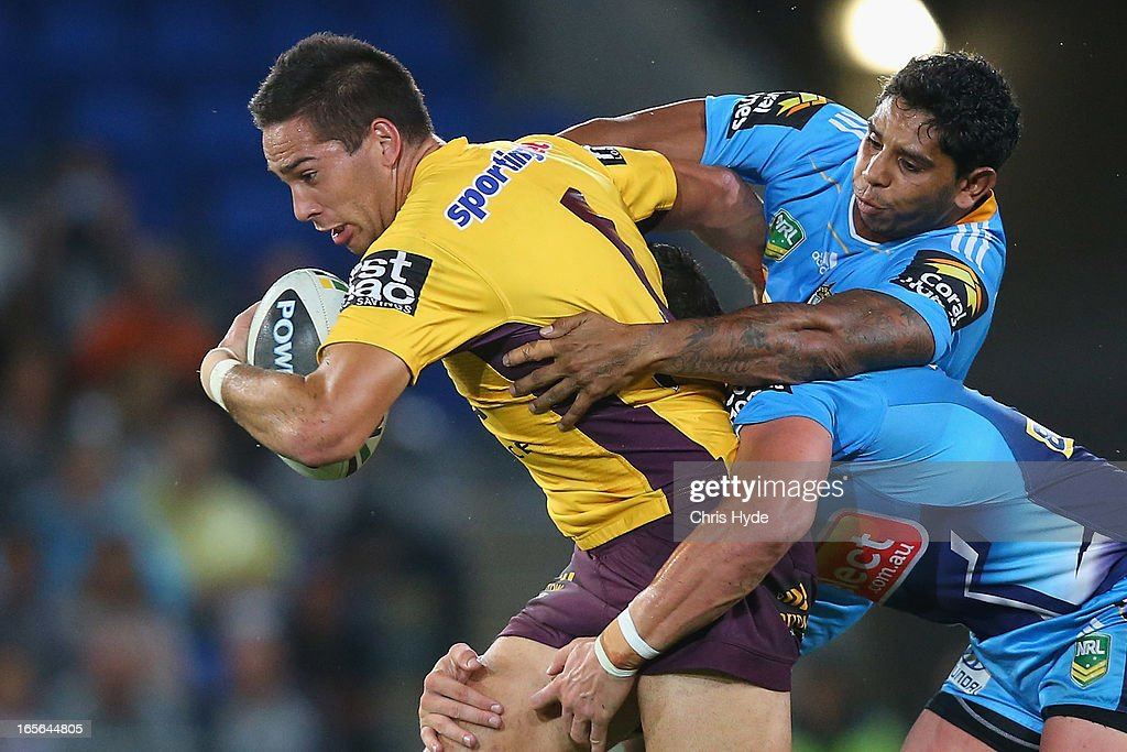 Corey Norman of the Broncos is tackled by Albert Kelly of the Titans during the round five NRL match between the Gold Coast Titans and the Brisbane Broncos at Skilled Park on April 5, 2013 in Gold Coast, Australia.