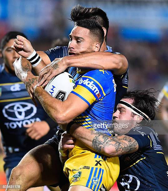 Corey Norman of the Eels is tackled by Ethan Lowe and James Tamou of the Cowboys during the round eight NRL match between the North Queensland...