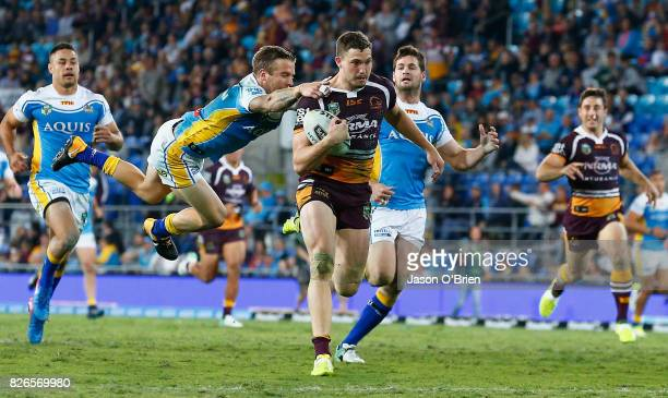 Corey Oates of the Broncos breaks the tackle of Kane Elgey to score a try during the round 22 NRL match between the Gold Coast Titans and the...