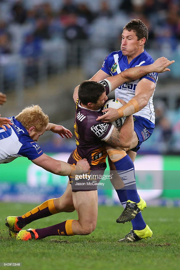 Corey Oates of the Broncos is tackled by Josh Jackson of the Bulldogs during the round 16 NRL match between the Canterbury Bulldogs and Brisbane Broncos at ANZ Stadium on June 25, 2016 in Sydney, Australia.