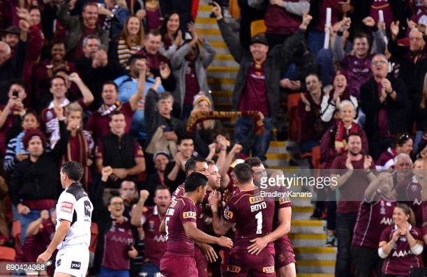 Corey Oates of the Maroons is congratulated by team mates after scoring a try during game one of the State Of Origin series between the Queensland...