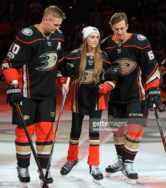 Corey Perry and Rickard Rakell of the Anaheim Ducks assist this year's '21st Duck' Katie Hawley prior to the game against the Arizona Coyotes on...