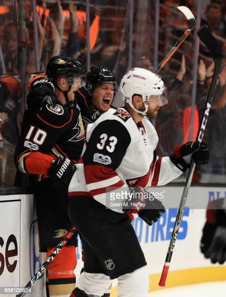 Corey Perry congratulates Rickard Rakell of the Anaheim Ducks after he scored a goal as Alex Goligoski of the Arizona Coyotes looks on during the...