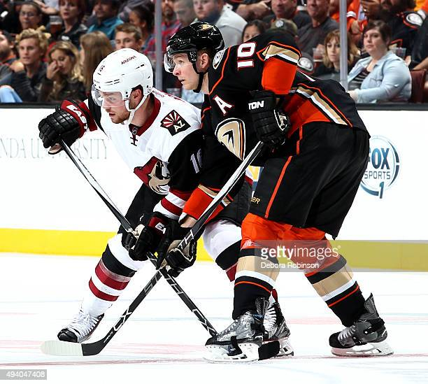 Corey Perry of the Anaheim Ducks and Max Domi of the Arizona Coyotes get into position during the game on October 14 2015 at Honda Center in Anaheim...