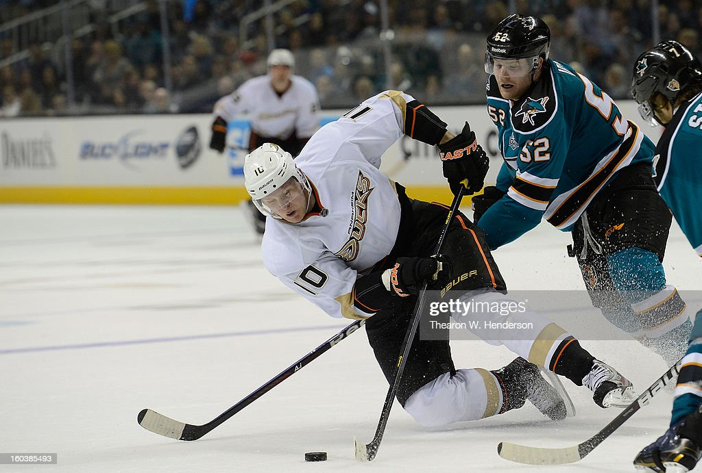 Corey Perry #10 of the Anaheim Ducks attempting to maintain control of the puck gets checked to the ice by Matt Irwin #52 of the San Jose Shark in the third period at HP Pavilion on January 29, 2013 in San Jose, California. The Sharks won the game in an overtime shoot-out.