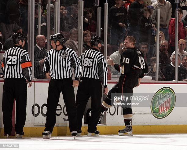 Corey Perry of the Anaheim Ducks goes to the penalty box in the second period against the Buffalo Sabres as referee Chris Lee and linesman Brad...