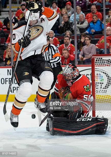 Corey Perry of the Anaheim Ducks jumps out of the way of the puck in front of goalie Corey Crawford of the Chicago Blackhawks resulting in the...