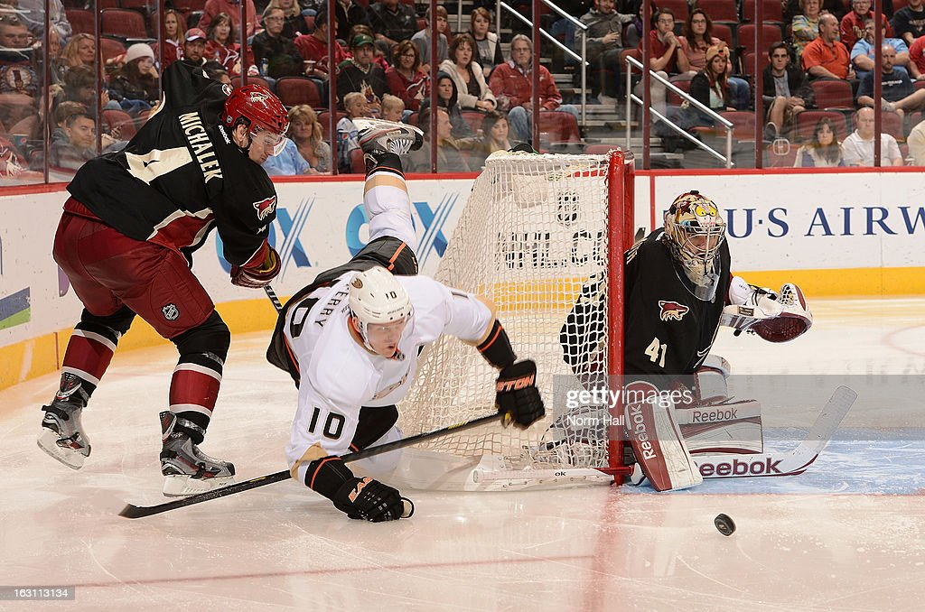 <a gi-track='captionPersonalityLinkClicked' href=/galleries/search?phrase=Corey+Perry&family=editorial&specificpeople=213864 ng-click='$event.stopPropagation()'>Corey Perry</a> #10 of the Anaheim Ducks looses the puck as he is tripped up by <a gi-track='captionPersonalityLinkClicked' href=/galleries/search?phrase=Zbynek+Michalek&family=editorial&specificpeople=243230 ng-click='$event.stopPropagation()'>Zbynek Michalek</a> #4 of the Phoenix Coyotes in front of goalie Mike Smith #41 during the third period at Jobing.com Arena on March 4, 2013 in Glendale, Arizona.