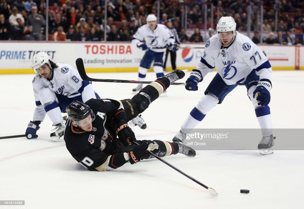 <a gi-track='captionPersonalityLinkClicked' href=/galleries/search?phrase=Corey+Perry&family=editorial&specificpeople=213864 ng-click='$event.stopPropagation()'>Corey Perry</a> #10 of the Anaheim Ducks lunges for the puck while falling to the ice between <a gi-track='captionPersonalityLinkClicked' href=/galleries/search?phrase=Mark+Barberio&family=editorial&specificpeople=4819242 ng-click='$event.stopPropagation()'>Mark Barberio</a> (L) #8 and <a gi-track='captionPersonalityLinkClicked' href=/galleries/search?phrase=Victor+Hedman&family=editorial&specificpeople=4784238 ng-click='$event.stopPropagation()'>Victor Hedman</a> #77 of the Tampa Bay Lightning at Honda Center on November 22, 2013 in Anaheim, California. The Ducks defeated the Lightning 1-0 in overtime.