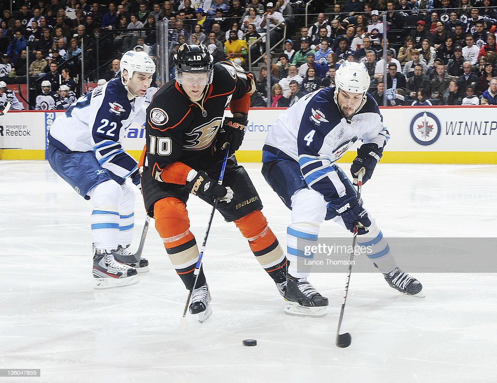 <a gi-track='captionPersonalityLinkClicked' href=/galleries/search?phrase=Corey+Perry&family=editorial&specificpeople=213864 ng-click='$event.stopPropagation()'>Corey Perry</a> #10 of the Anaheim Ducks plays the puck as he positions himself between <a gi-track='captionPersonalityLinkClicked' href=/galleries/search?phrase=Zach+Bogosian&family=editorial&specificpeople=4195061 ng-click='$event.stopPropagation()'>Zach Bogosian</a> #4 and <a gi-track='captionPersonalityLinkClicked' href=/galleries/search?phrase=Chris+Thorburn&family=editorial&specificpeople=2222066 ng-click='$event.stopPropagation()'>Chris Thorburn</a> #22 during third period at the MTS Centre on December 17, 2011 in Winnipeg, Manitoba, Canada.