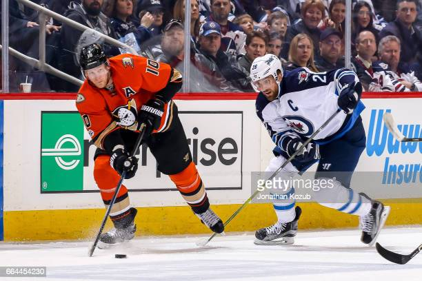 Corey Perry of the Anaheim Ducks plays the puck down the ice as Blake Wheeler of the Winnipeg Jets gives chase during first period action at the MTS...
