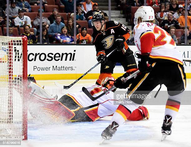 Corey Perry of the Anaheim Ducks scores on a fallen Jonas Hiller of the Calgary Flames for a 10 lead as Dougie Hamilton looks on during the first...