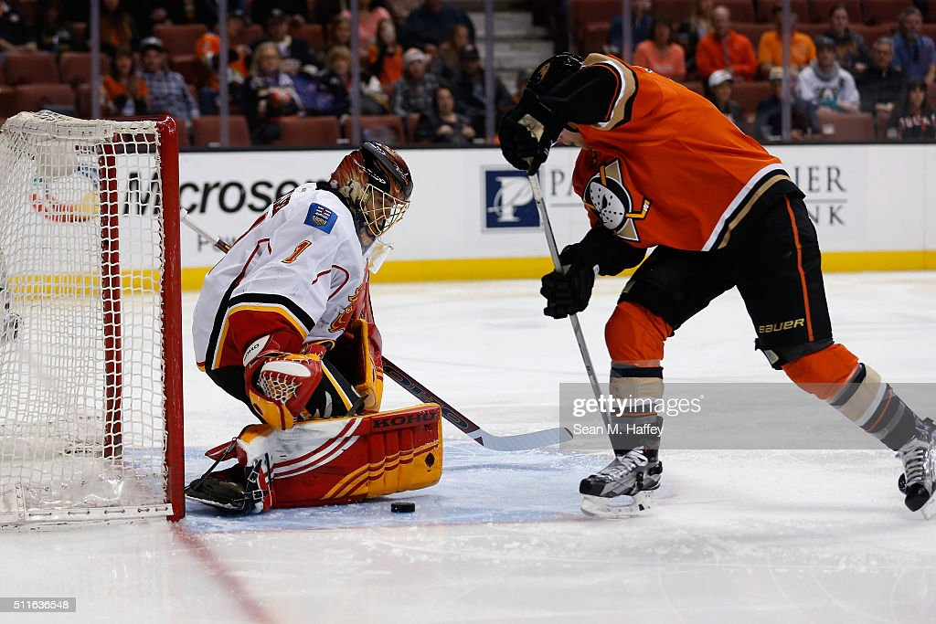 Corey Perry #10 of the Anaheim Ducks shoots the puck as Jonas Hiller #1 of the Calgary Flames blocks the shot during the first period of a game at Honda Center on February 21, 2016 in Anaheim, California.