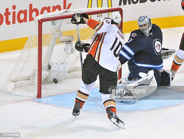 Corey Perry of the Anaheim Ducks shoots the puck past goaltender Ondrej Pavelec of the Winnipeg Jets for a second period goal in Game Three of the...