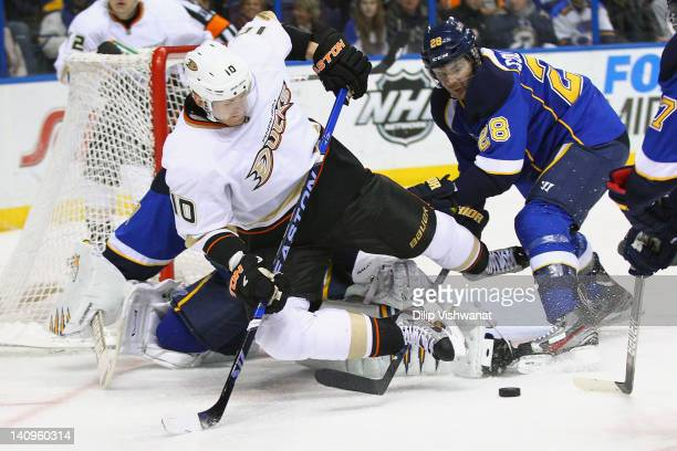 Corey Perry of the Anaheim Ducks trips over Carlo Colaiacovo of the St Louis Blues in front of the net at the Scottrade Center on March 8 2012 in St...