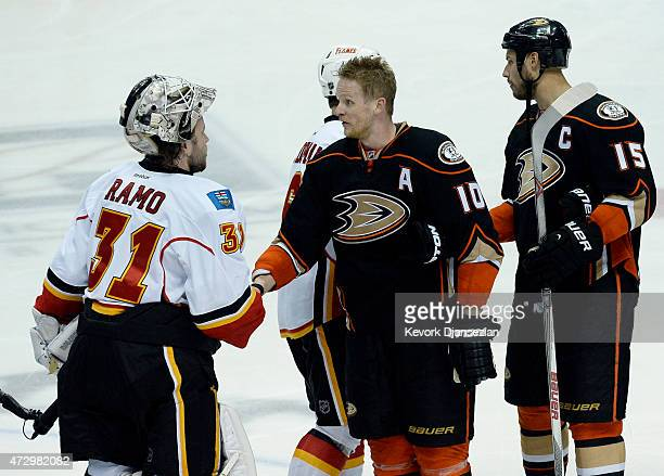 Corey Perry of the Anaheim Ducks who scored the game winning goal in overtime shakes hands with Karri Ramo of the Calgary Flames while teammate Ryan...