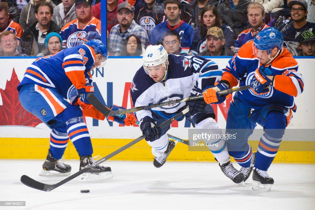 <a gi-track='captionPersonalityLinkClicked' href=/galleries/search?phrase=Corey+Potter&family=editorial&specificpeople=2339200 ng-click='$event.stopPropagation()'>Corey Potter</a> #44 of the Edmonton Oilers tries to check <a gi-track='captionPersonalityLinkClicked' href=/galleries/search?phrase=Devin+Setoguchi&family=editorial&specificpeople=2221039 ng-click='$event.stopPropagation()'>Devin Setoguchi</a> #40 of the Winnipeg Jets during an NHL game at Rexall Place on December 23, 2013 in Edmonton, Alberta, Canada. The Oilers defeated the Jets 6-2.