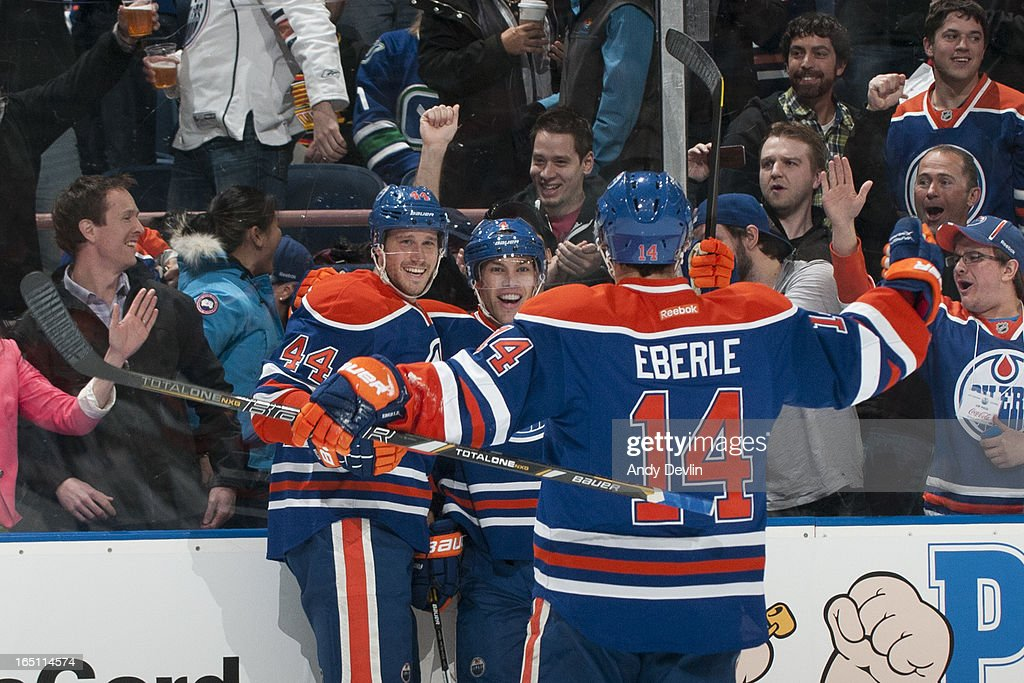 Corey Potter #44, Taylor Hall #4 , and Jordan Eberle #14 of the Edmonton Oilers celebrate after scoring a goal in a game against the Vancouver Canucks on March 30, 2013 at Rexall Place in Edmonton, Alberta, Canada.