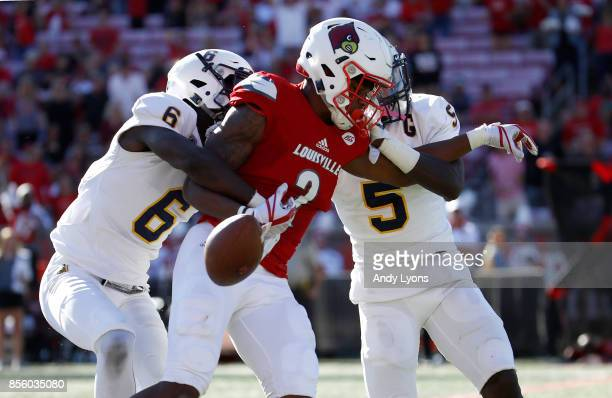 Corey Reed of the Louisville Cardinals fumbles the ball while tackled by Marquez Sanford and D'Montre Wade of the Murray State Racers during the game...