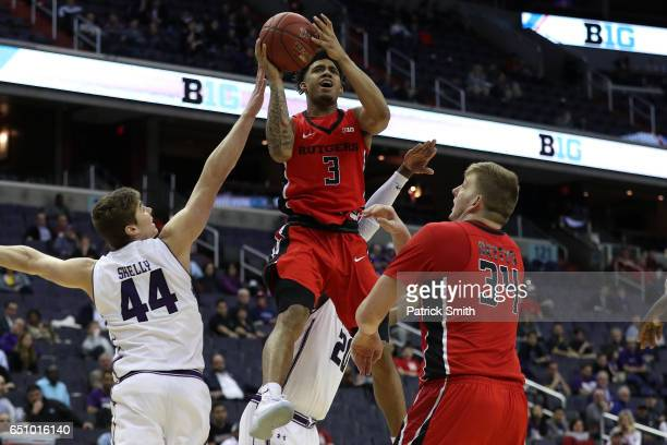 Corey Sanders of the Rutgers Scarlet Knights shoots in front of Gavin Skelly of the Northwestern Wildcats during the second half in the second round...