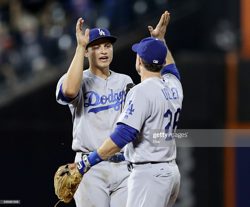 Corey Seager #5 and Chase Utley #26 of the Los Angeles Dodgers celebrate the 9-1 win over the New York Mets at Citi Field on May 28, 2016 in the Flushing neighborhood of the Queens borough of New York City.