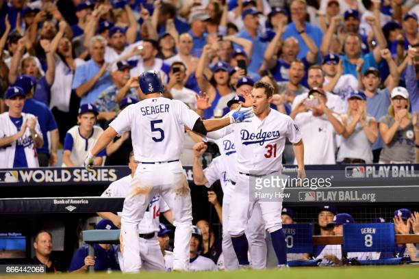 Corey Seager of the Los Angeles Dodgers celebrates at the dugout with Joc Pederson after hitting a tworun home run during the sixth inning against...
